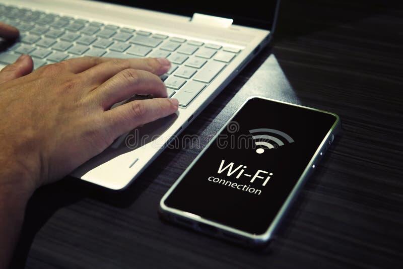 Feche acima das mãos masculinas que datilografam no teclado numérico do portátil e que verificam a conexão de Wi-Fi do smartphone imagens de stock royalty free