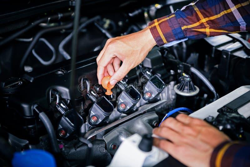 Feche acima das mãos que verificam o nível do óleo lubrificante de motor de automóveis de profundo-s fotografia de stock
