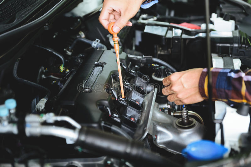 Feche acima das mãos que verificam o nível do óleo lubrificante de motor de automóveis de profundo-s fotos de stock royalty free