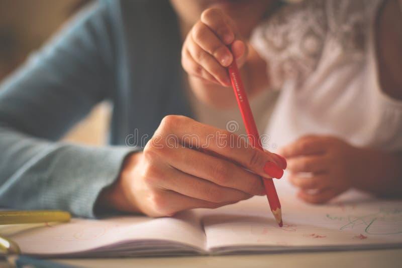 Feche acima das mãos serem de mãe a uma menina que escreve junto fotografia de stock royalty free
