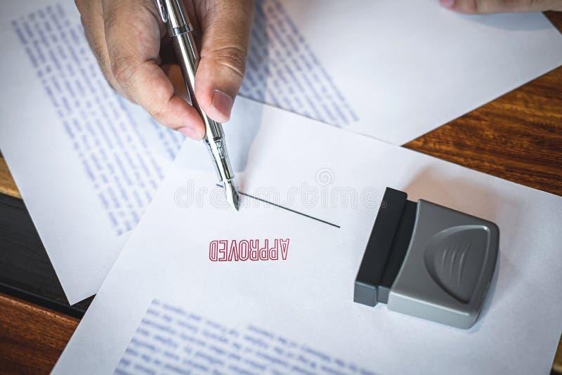 Feche acima das m?os da assinatura e do selo do homem de neg?cios no documento de papel para aprovar o acordo de contrato do inve fotos de stock