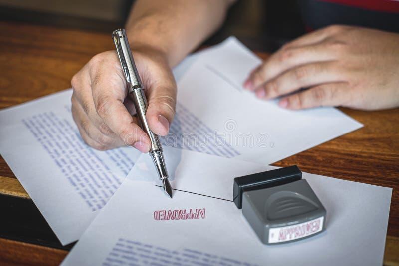 Feche acima das m?os da assinatura e do selo do homem de neg?cios no documento de papel para aprovar o acordo de contrato do inve foto de stock