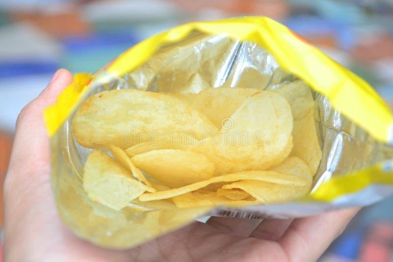 Feche acima das microplaquetas de batata no saco aberto fotografia de stock