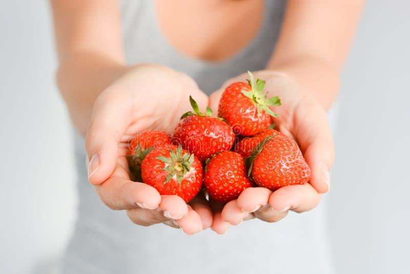 Feche acima das morangos vermelhas frescas com licença verde na mão da mulher imagem de stock