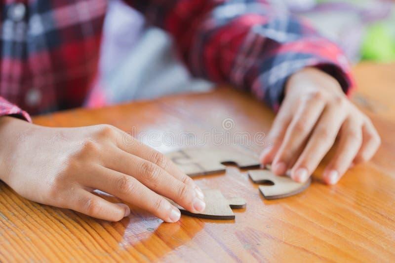 Feche acima das mulheres de negócio das mãos que conectam o puzzleon da serra de vaivém, chá imagens de stock royalty free