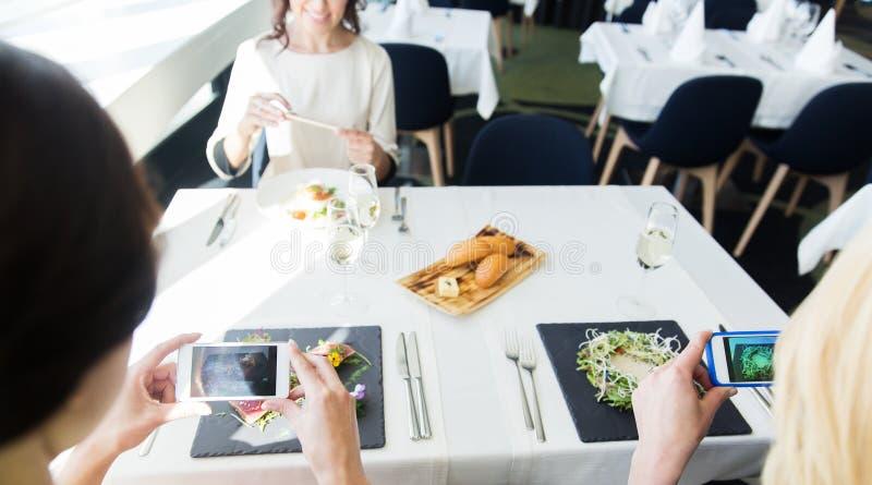 Feche acima das mulheres que representam o alimento por smartphones foto de stock