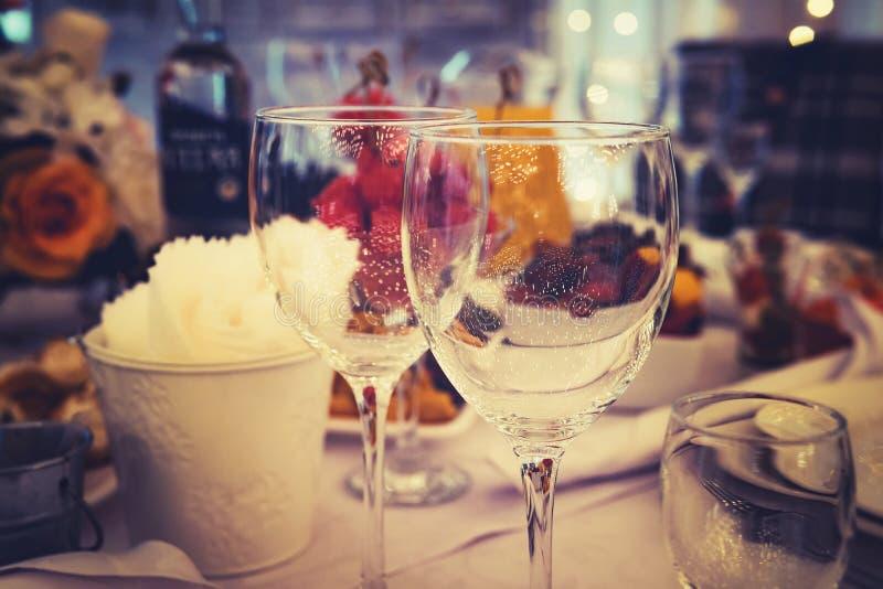 Feche acima das nomeações de tabela em um partido de jantar formal Stemwares em uma tabela belamente decorada festiva do casament foto de stock