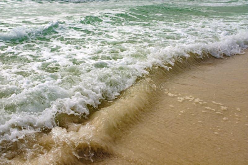 Feche acima das ondas que deixam de funcionar delicadamente em uma praia tropical bonita imagens de stock