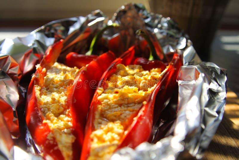 Feche acima das pimentas de sino vermelhas enchidas da paprika com o queijo de feta dos carneiros temperado com o pimentão picant imagem de stock