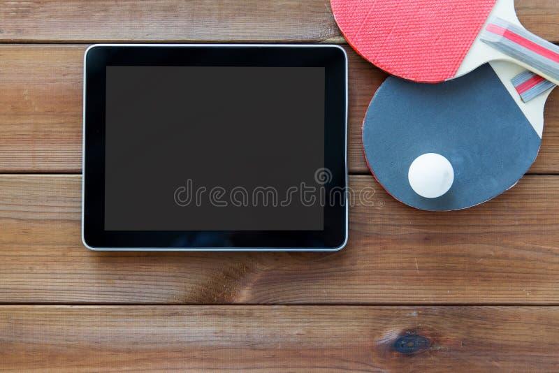 Feche acima das raquetes de tênis de mesa e do PC da tabuleta fotografia de stock royalty free