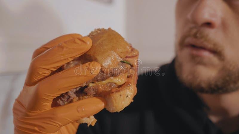 Feche acima das sobras do homem novo hangry do Hamburger à disposição fotografia de stock royalty free