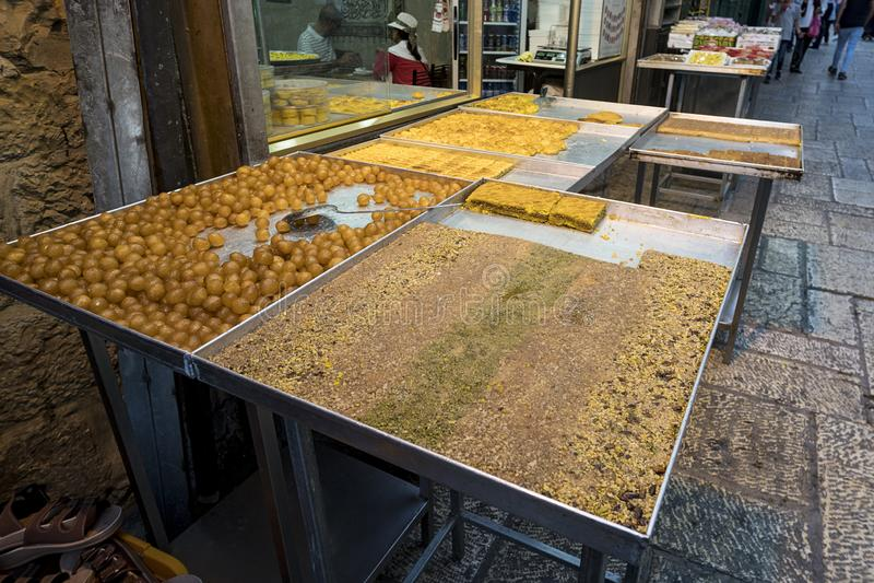 Feche acima das tendas com frutos doces e a pastelaria expostos para a venda perto de algum café do alimento da rua no Jerusalém  imagem de stock royalty free