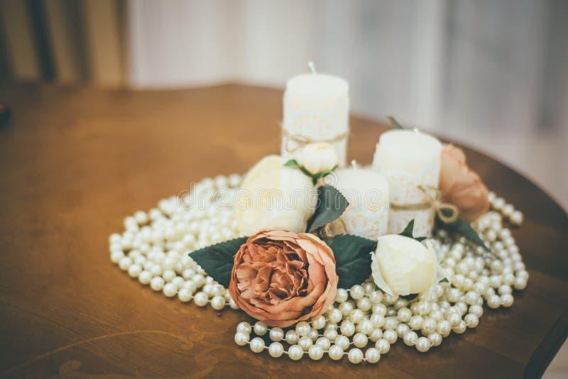 Feche acima das velas do casamento cercadas com pérolas e rosas fotos de stock