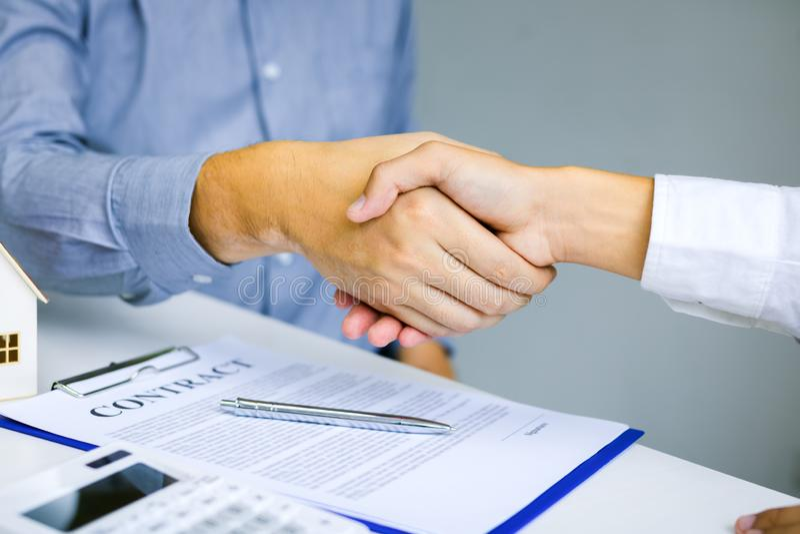 Feche acima de agitar as mãos com cliente e corretor imobiliário após ter assinado um contrato no escritório domiciliário fotos de stock royalty free