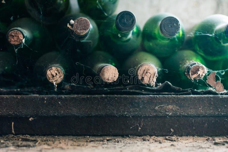Feche acima de algumas garrafas de vinho muito velhas e empoeiradas em uma adega de vinho fotos de stock