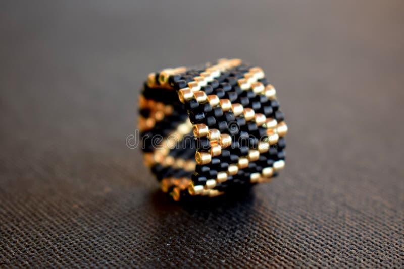 Feche acima de anel frisado em uma tabela preta, teste padrão geométrico imagens de stock
