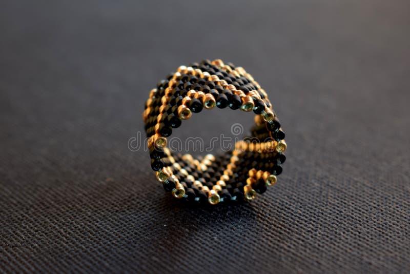 Feche acima de anel frisado em uma tabela preta, teste padrão geométrico fotografia de stock royalty free