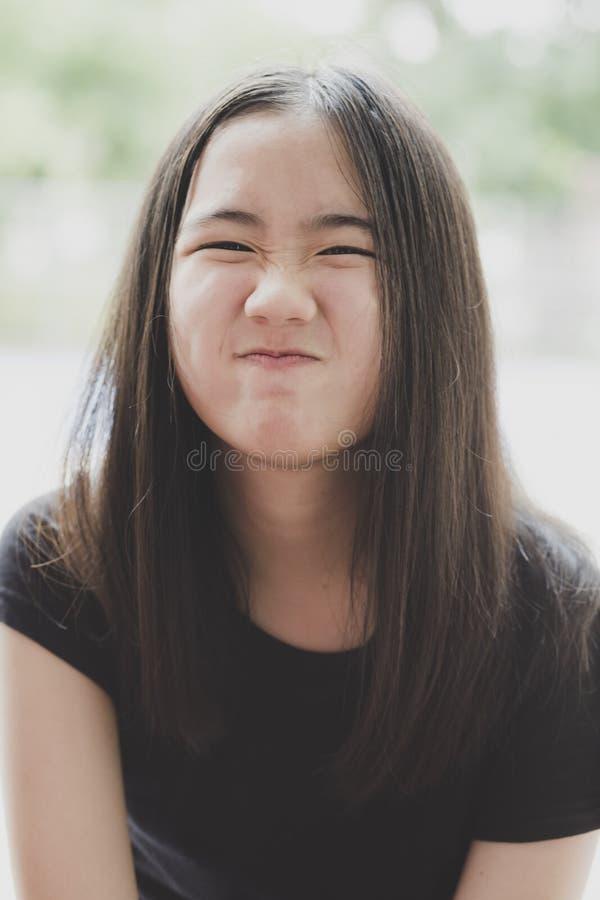 Feche acima de caçoar a cara do adolescente asiático alegre com cabelo marrom longo fotos de stock