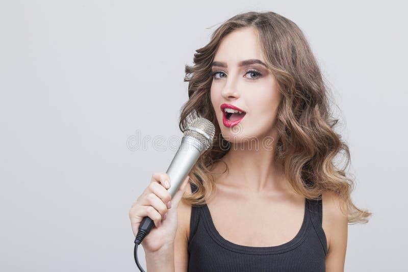 Feche acima de cantar a mulher de cabelo marrom na sala cinzenta imagem de stock royalty free