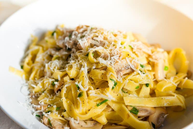 Feche acima de convidar o prato caseiro italiano da massa dos tagliatelle com cogumelo e queijo parmesão na tabela com pano fotos de stock royalty free