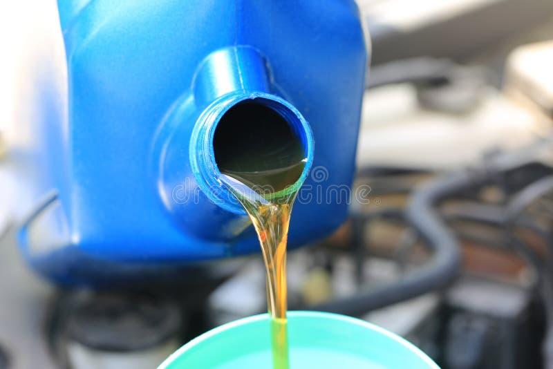 Feche acima de derramar o óleo fresco ao motor de automóveis no serviço de reparação de automóveis, óleo da mudança fotografia de stock royalty free
