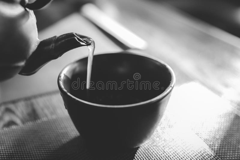 Feche acima de derramar uma chaleira de chá verde japonesa quente em um copo oriental do estilo na tabela foto de stock