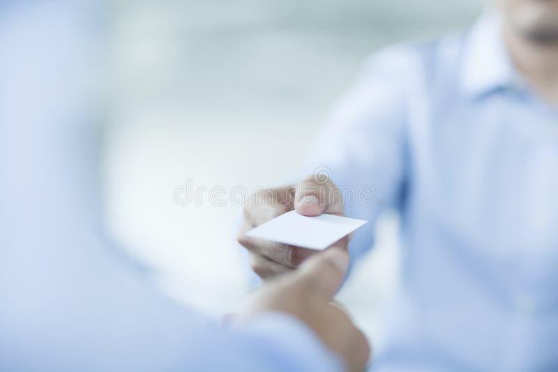 Feche acima de dois homens de negócios que trocam cartões foto de stock royalty free