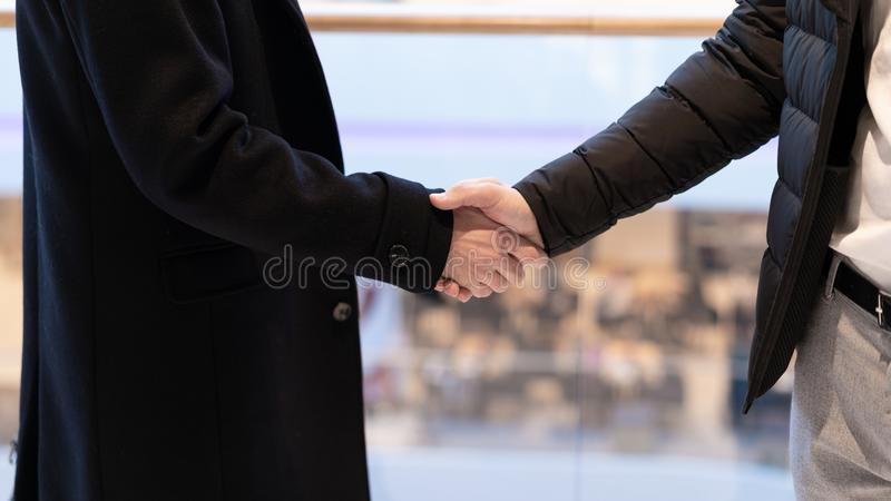Feche acima de dois homens de negócios bem sucedidos que cumprimentam-se na perspectiva do olhar na cidade Aperto de mão do negóc foto de stock