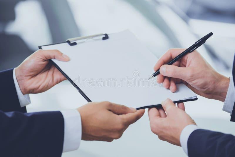Feche acima de dois homens que assinam o contrato na sala de exposições do carro foto de stock
