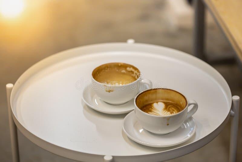 Feche acima de dois sujos e dos copos brancos vazios do latte quente do café branco redonda imagens de stock