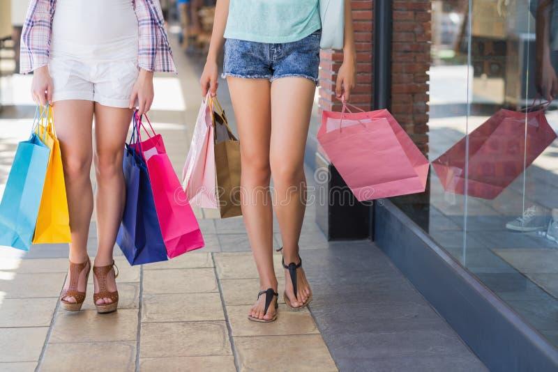 Feche acima de duas mulheres que andam com sacos de compras fotos de stock