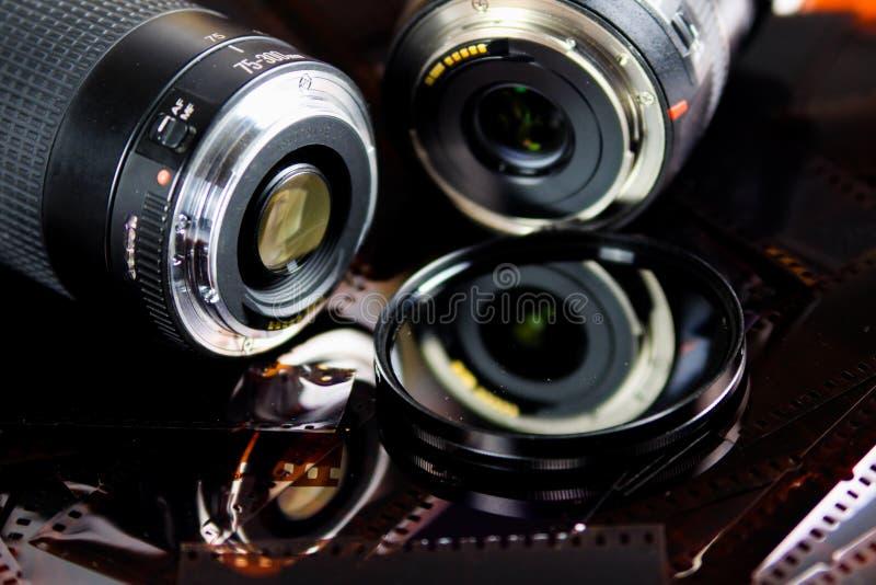 Feche acima de duas objetivas com o filtro circular isolado em tiras do filme negativo imagens de stock