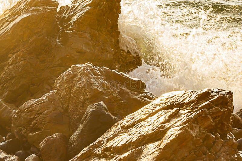 Feche acima de espirrar a onda em pedregulhos e em rochas molhados ensolarados de incandesc?ncia foto de stock