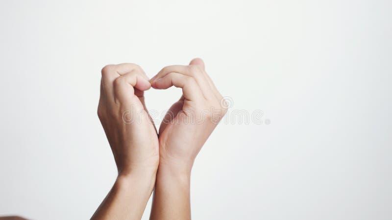 Feche acima de fazer o coração das mãos fêmeas em um fundo branco imagem de stock