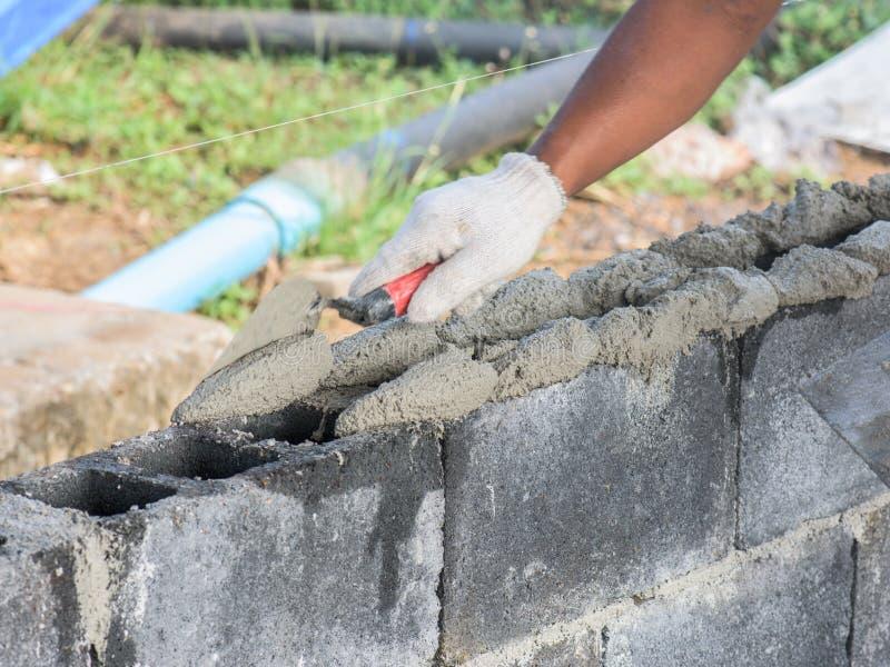 Feche acima de instalar tijolos no canteiro de obras pelo pedreiro industrial imagens de stock