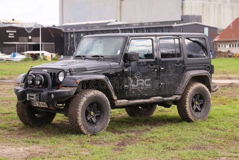 Feche acima de Jeep Wrangler sujo após ter conduzido fora de estrada pesado no terreno molhado Rodas sujadas na lama e na sujeira fotografia de stock royalty free
