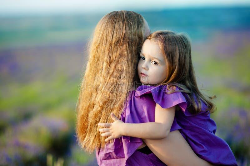 Feche acima de mãe loving e do bebê que levantam no campo de florescência imagem de stock royalty free
