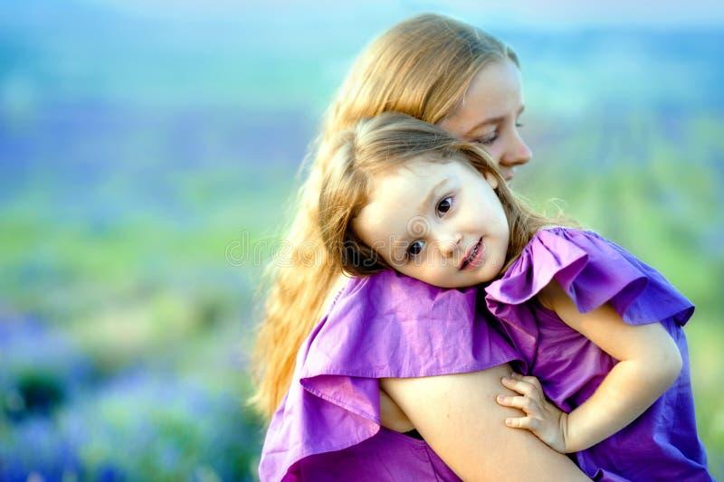 Feche acima de mãe loving e do bebê que levantam no campo de florescência fotografia de stock royalty free