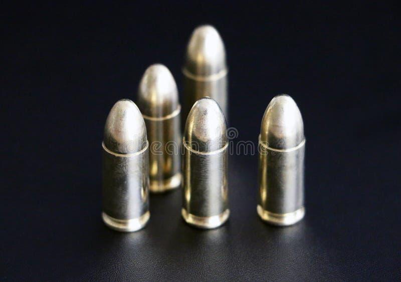 Feche acima de 9 milímetros de munição dourada das balas da pistola no fundo imagens de stock