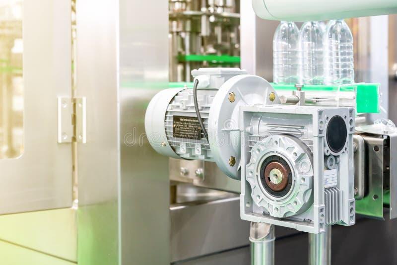 Feche acima de moderno da caixa de engrenagens e o motor elétrico instala na máquina automática da injeção da garrafa para o tran foto de stock