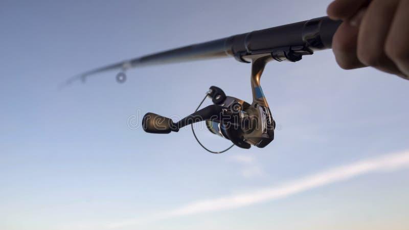 Feche acima de pescar o carretel, peixe de travamento do homem com haste de gerencio à disposição, engrenagem foto de stock royalty free