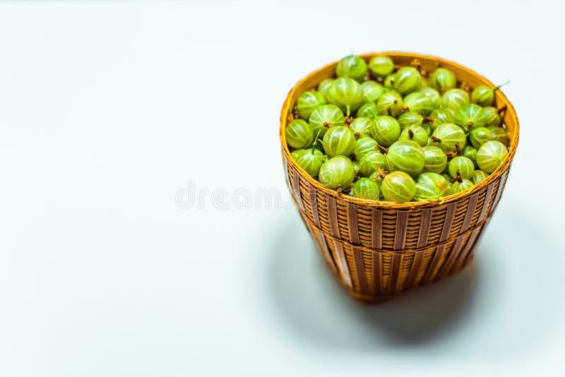 Feche acima de pouca cesta com a groselha verde no branco imagens de stock royalty free