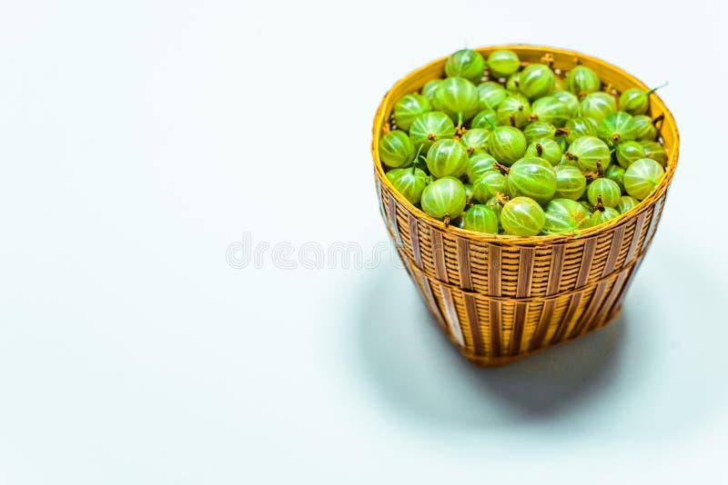 Feche acima de pouca cesta com a groselha verde no branco fotografia de stock