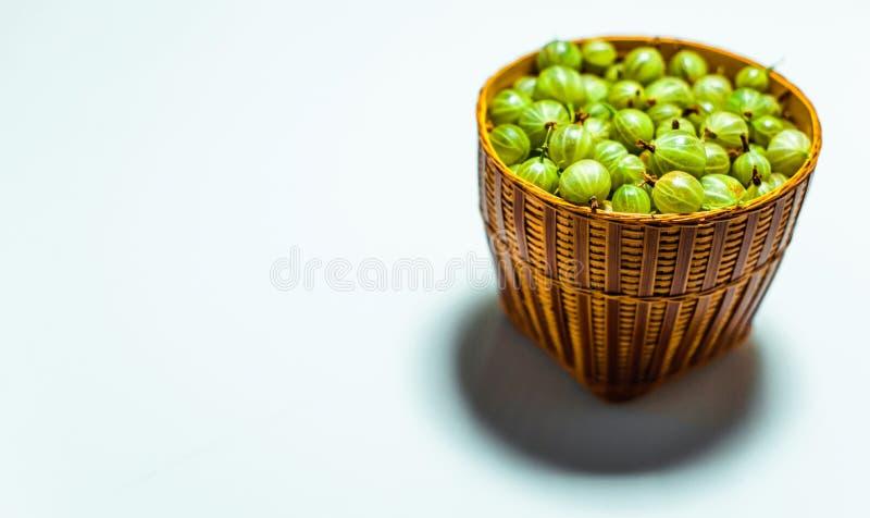 Feche acima de pouca cesta com a groselha verde no branco foto de stock