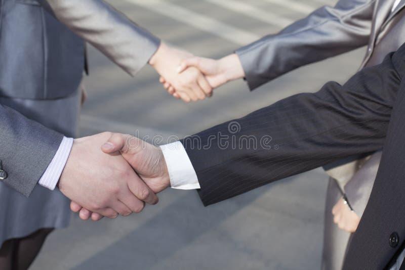 Feche acima de quatro executivos que agitam as mãos fotos de stock