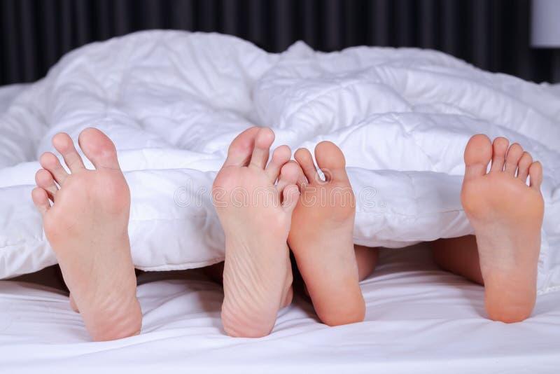 Feche acima de quatro pés na cama imagens de stock royalty free
