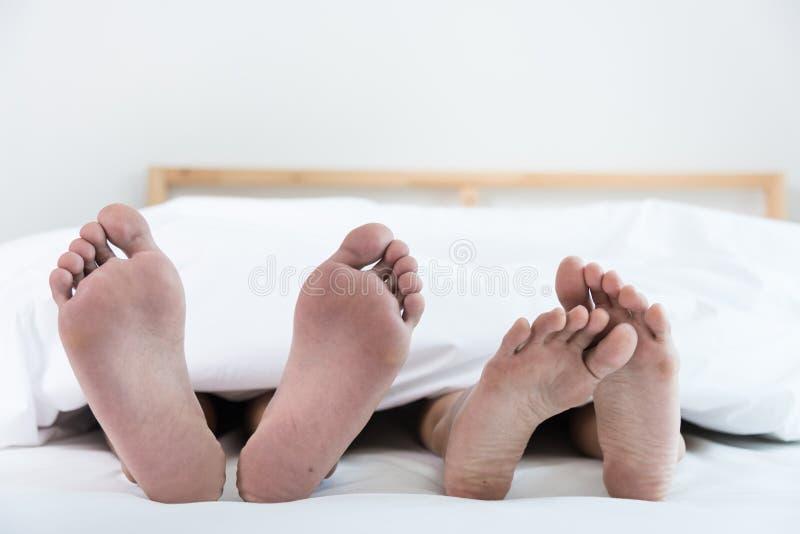 Feche acima de quatro pés na cama foto de stock royalty free