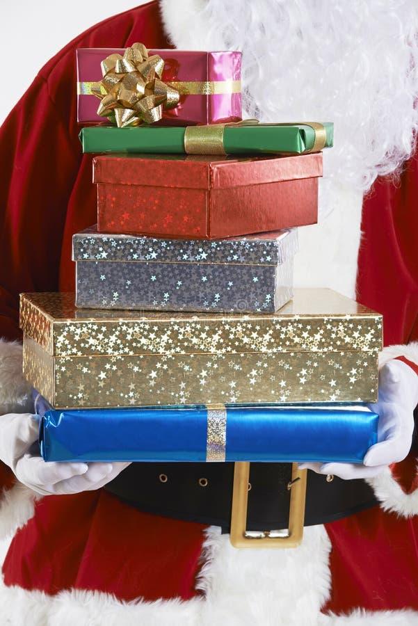 Feche acima de Santa Claus Holding Pile Of Gift envolveu presentes imagens de stock