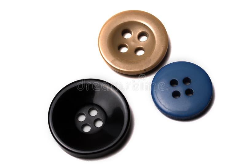 Feche acima de três botões Preto, ouro, azul na cor fotografia de stock royalty free