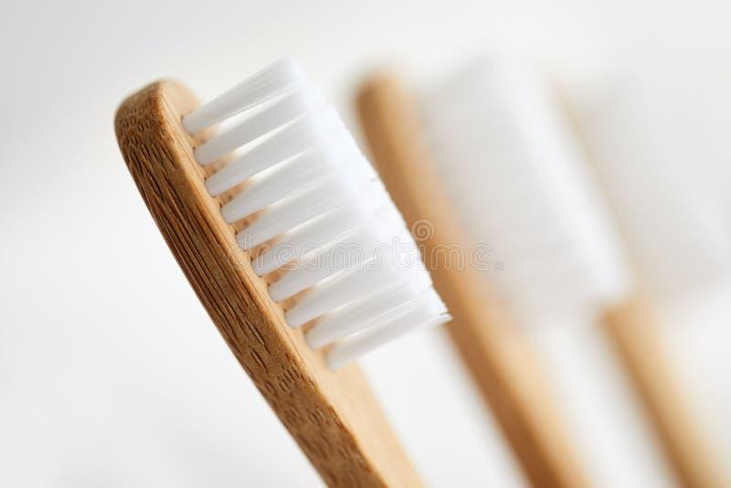 Feche acima de três escovas de dentes de bambu foto de stock